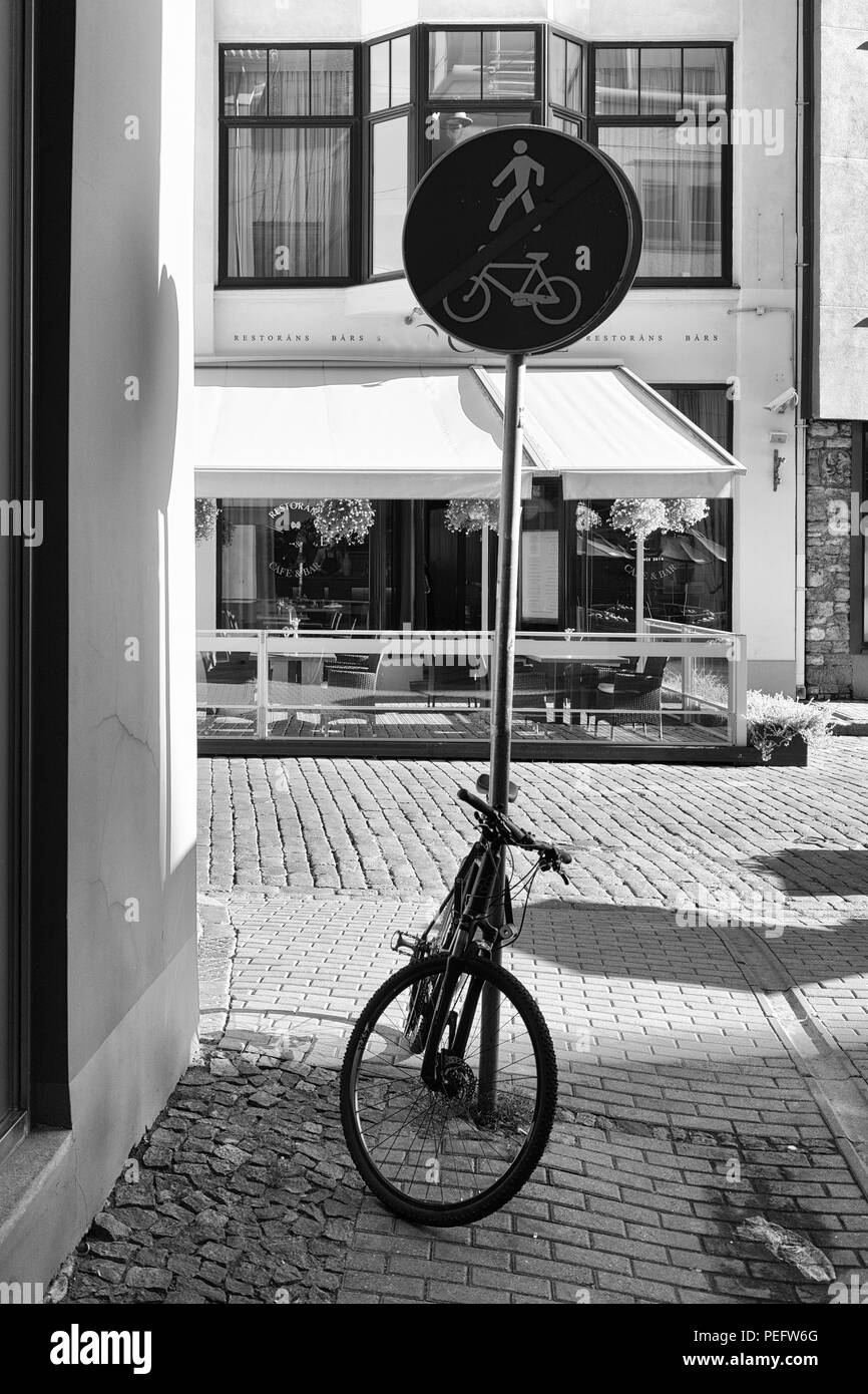 Latvia, Riga. Bicycle parked in the pedestrian zone end sign on the background of the summer terrace cafe - Stock Image
