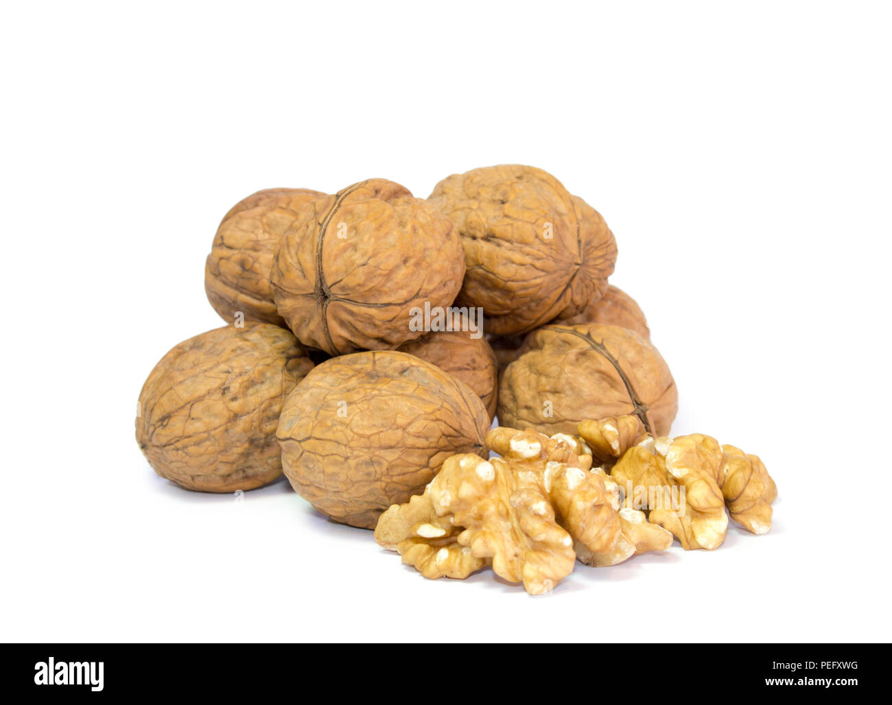 Horizontal photo of couple of walnut kernels in front of pile of walnut shells isolated on white background. Healthy and tasty snacks. - Stock Image