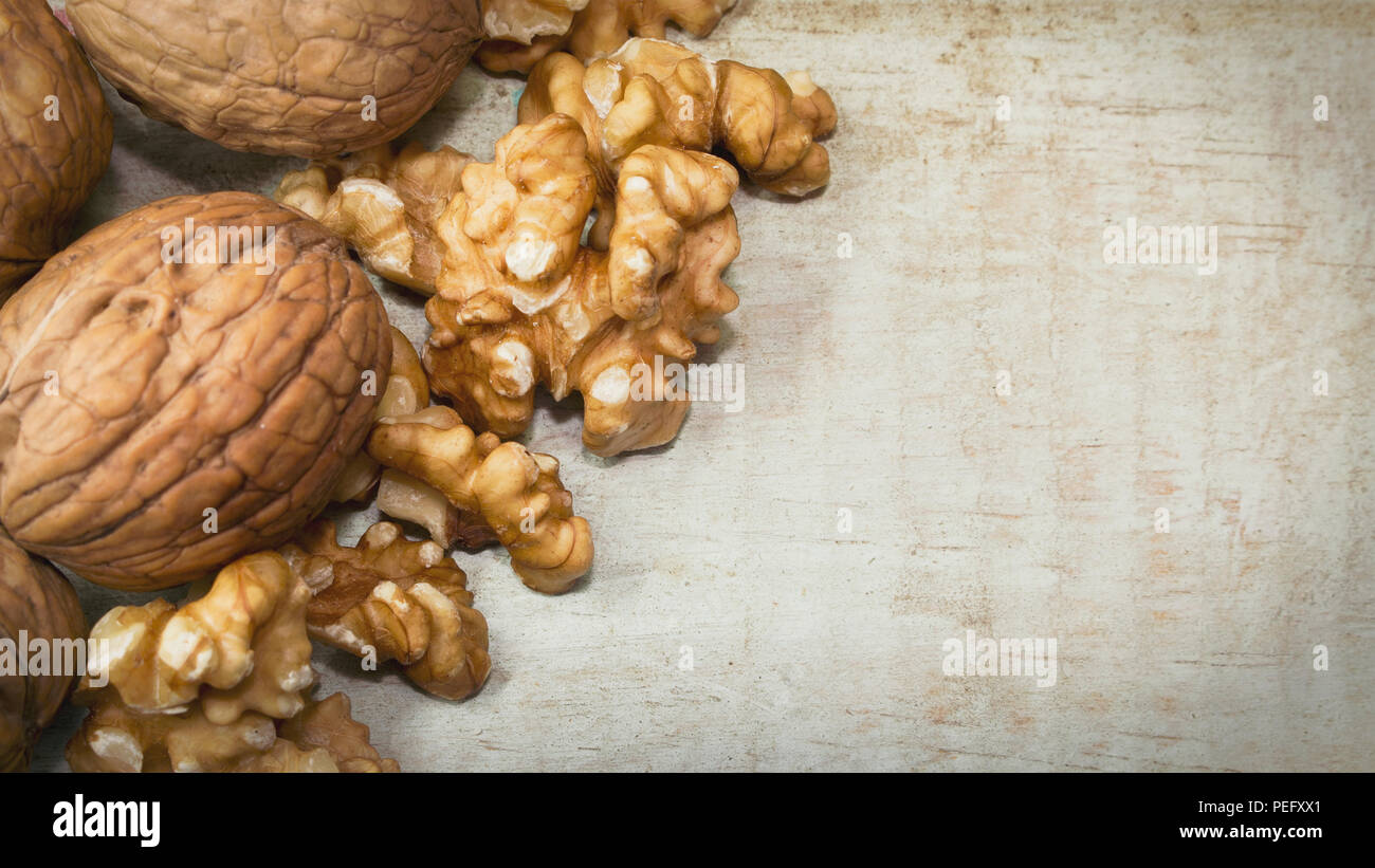 Horizontal close up photo of mix of walnut shells and walnuts kernels on light wooden surface, with space for copy. - Stock Image