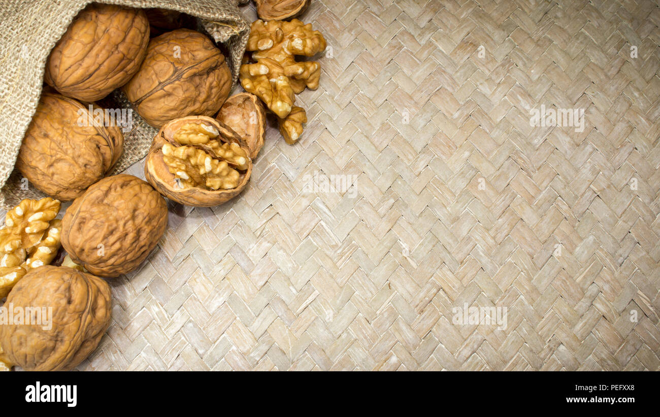 Horizontal photo of an arrangment of walnuts shells and walnut kernels in burlap sack on light wicker surface, with space for copy. - Stock Image