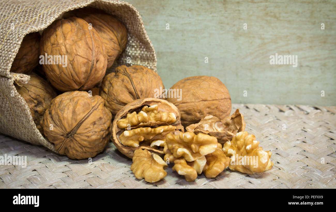 Horizontal photo of walnut shells and walnut kernels bursting out of burlap sack on wicker surface. - Stock Image