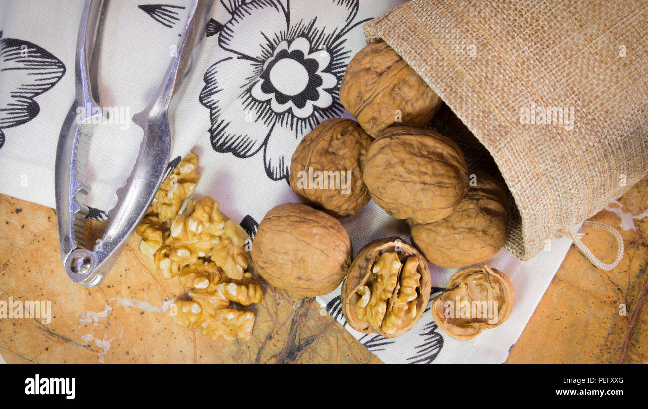 Horizontal photo of walnut shells and kernels in burlap sack on marble surface with white towel with flowers. Nutcracker next to walnuts. - Stock Image