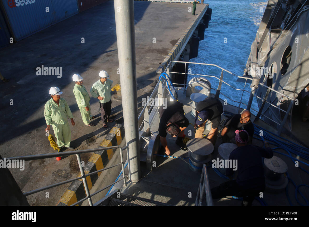 150817-M-GO800-100 DA NANG, Vietnam (August 17, 2015) – Civilian Mariners work alongside Vietnamese dock workers to secure the Military Sealift Command joint high speed vessel USNS Millinocket (JHSV 3) to the pier Aug. 17. Task Force Forager, embarked aboard Millinocket is serving as the secondary platform for Pacific Partnership, led by an expeditionary command element from the Navy's 30th Naval Construction Regiment (30 NCR) from Port Hueneme, California. Now in its 10th iteration, Pacific Partnership is the largest annual multilateral humanitarian assistance and disaster relief preparedness - Stock Image