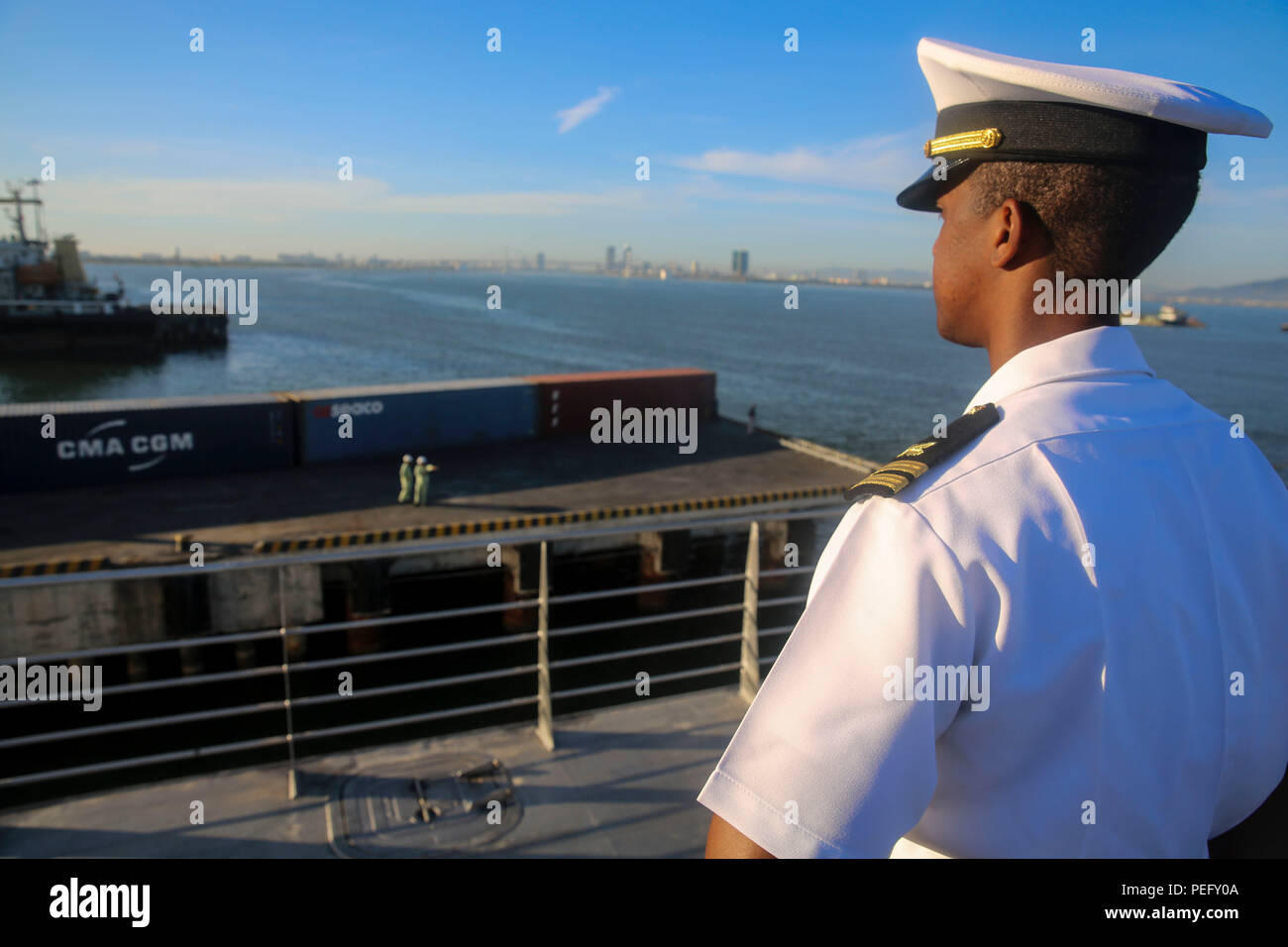 150817-M-GO800-055 DA NANG, Vietnam (August 17, 2015) – Lt. Orlando White mans the rails aboard the Military Sealift Command joint high speed vessel USNS Millinocket (JHSV 3) Aug. 17 as the ship arrives in Vietnam. Task Force Forager, embarked aboard Millinocket is serving as the secondary platform for Pacific Partnership, led by an expeditionary command element from the Navy's 30th Naval Construction Regiment (30 NCR) from Port Hueneme, California. Now in its 10th iteration, Pacific Partnership is the largest annual multilateral humanitarian assistance and disaster relief preparedness mission - Stock Image