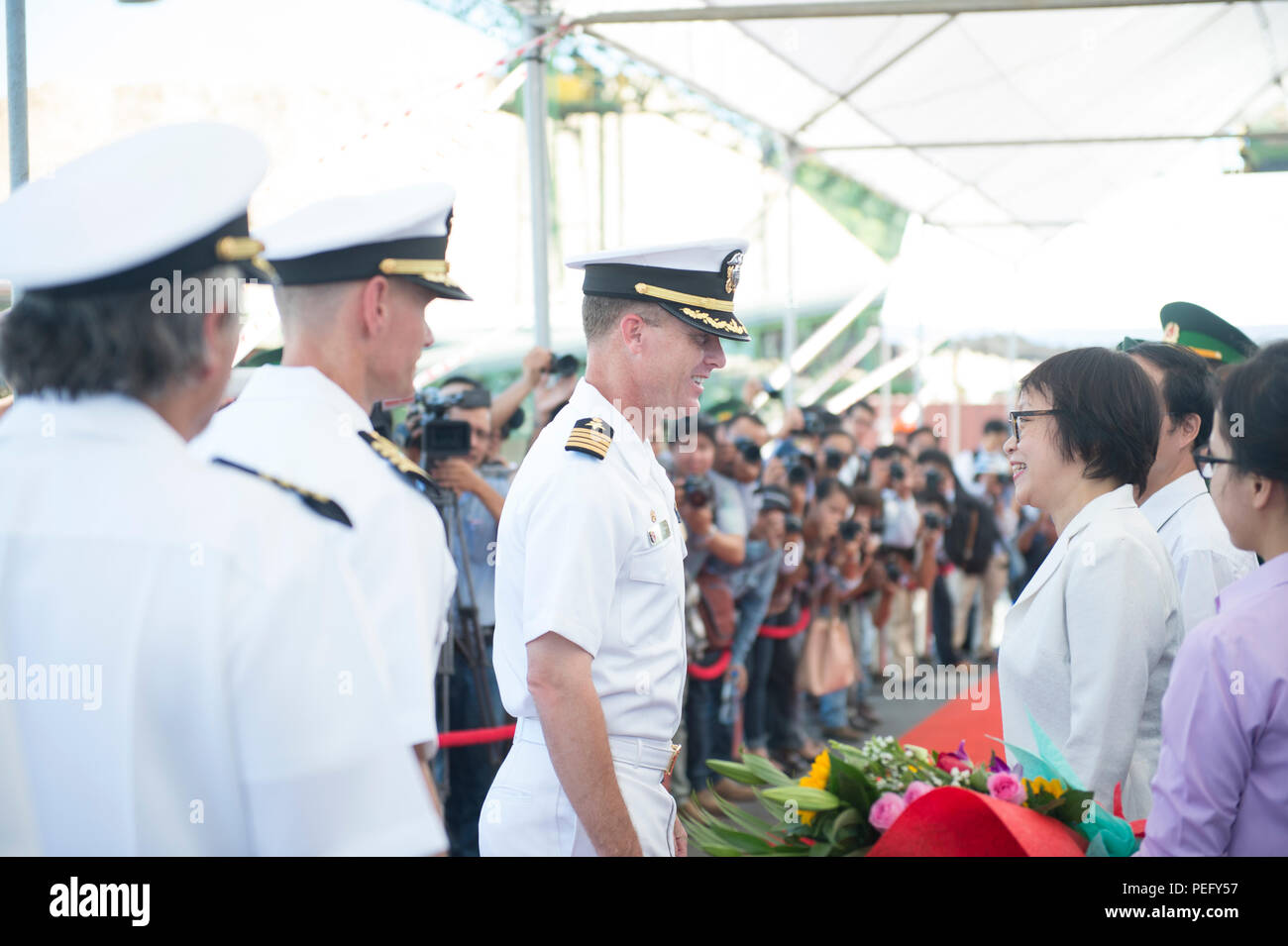 150817-N-MK341-027 DA NANG, Vietnam (Aug.t 17, 2015) – Commodore, Pacific Partnership Capt. Chris Engdahl greets a representative from the De Nang People's Committee Aug.t 17.  Vietnam is the fifth stop for the Military Sealift Command joint high speed vessel USNS Millinocket (JHSV 3) and embarked Task Force Forager. Millinocket and embarked Task Force Forager are serving as the secondary platform for Pacific Partnership, led by an expeditionary command element from the Navy's 30th Naval Construction Regiment (30 NCR) from Port Hueneme, Calif. Now in its 10th iteration, Pacific Partnership is  - Stock Image