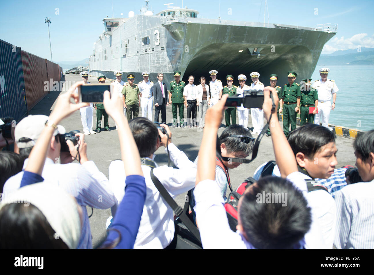 150817-N-MK341-141 DA NANG, Vietnam (Aug. 17, 2015) – Pacific Partnership leadership alongside local government officials pause for a photo in front of the Military Sealift Command joint high speed vessel USNS Millinocket (JHSV 3). Vietnam is the fifth stop for Millinocket and embarked Task Force Forager. Millinocket and embarked Task Force Forager are serving as the secondary platform for Pacific Partnership, led by an expeditionary command element from the Navy's 30th Naval Construction Regiment (30 NCR) from Port Hueneme, Calif. Now in its 10th iteration, Pacific Partnership is the largest  - Stock Image