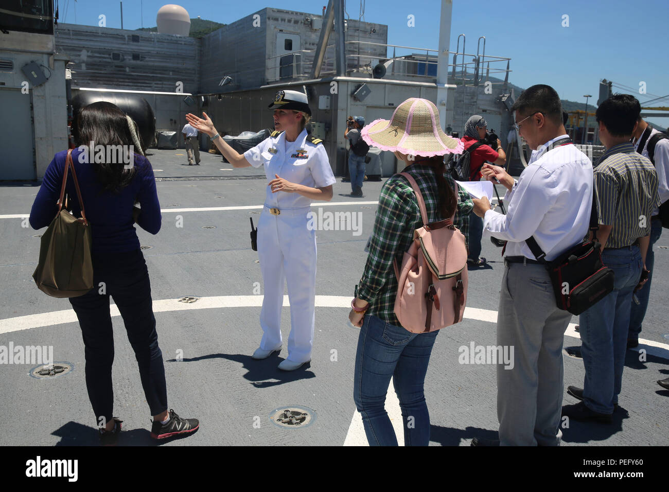 150817-M-GO800-324 DA NANG, Vietnam (Aug. 17, 2015) – Lt. Chelsea Irish explains to local Vietnamese news media the function of the flight deck aboard the Military Sealift Command joint high speed vessel USNS Millinocket (JHSV 3) during a ship tour August 17. Task Force Forager, embarked aboard the Millinocket  is serving as the secondary platform for Pacific Partnership, led by an expeditionary command element from the Navy's 30th Naval Construction Regiment (30 NCR) from Port Hueneme, Calif. Now in its 10th iteration, Pacific Partnership is the largest annual multilateral humanitarian assist - Stock Image