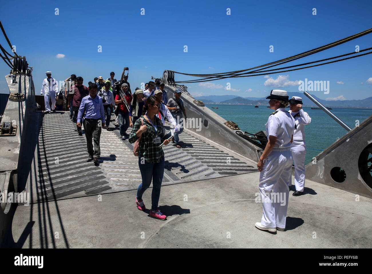 150817-M-GO800-236 DA NANG, Vietnam (Aug. 17, 2015) – Lt. Chelsea Irish leads local Vietnamese news media up the ramp of the Military Sealift Command joint high speed vessel USNS Millinocket (JHSV 3) during a ship tour Aug. 17. Task Force Forager, embarked aboard the Millinocket  is serving as the secondary platform for Pacific Partnership, led by an expeditionary command element from the Navy's 30th Naval Construction Regiment (30 NCR) from Port Hueneme, Calif. Now in its 10th iteration, Pacific Partnership is the largest annual multilateral humanitarian assistance and disaster relief prepare - Stock Image