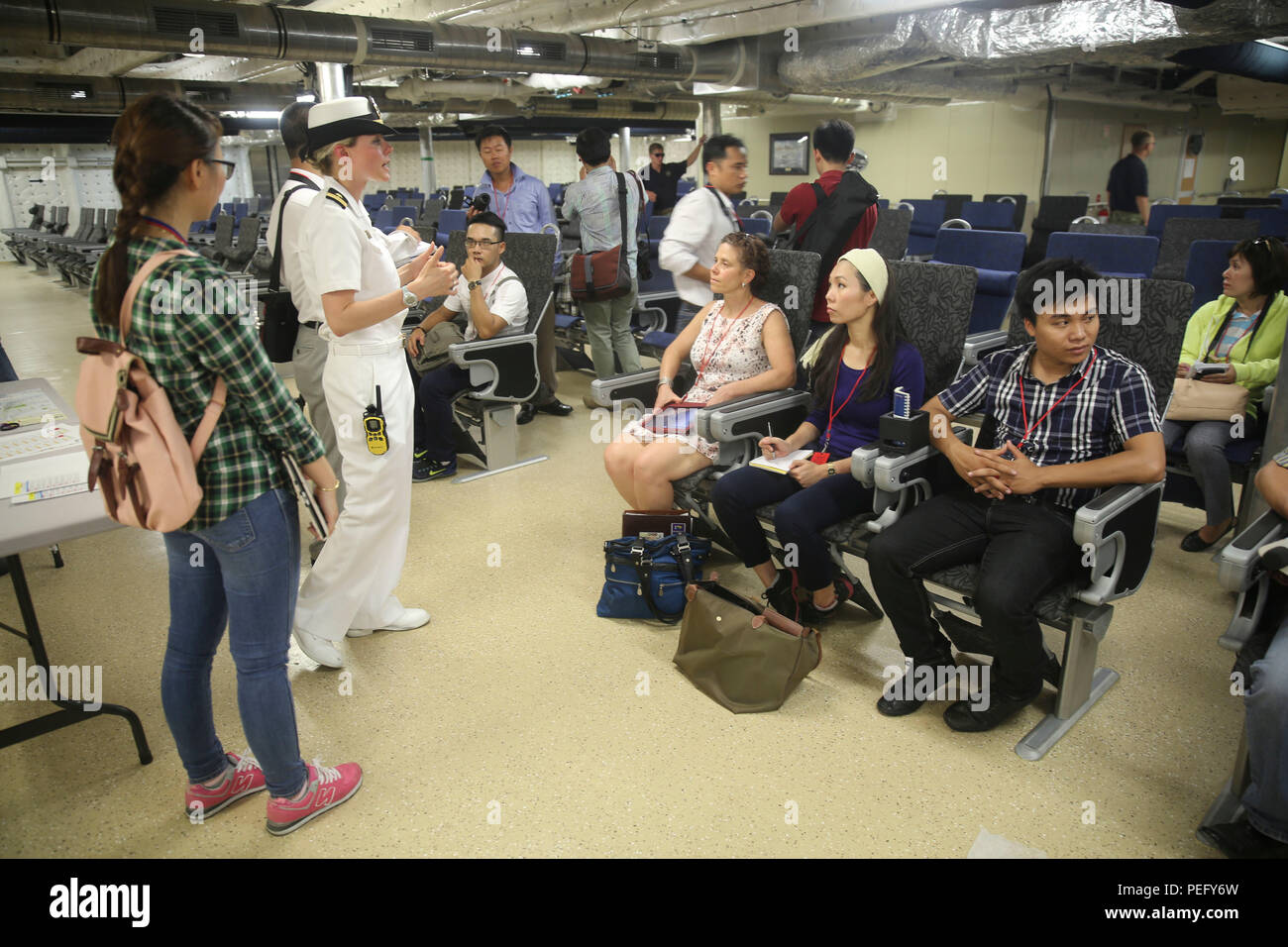 150817-M-GO800-258 DA NANG, Vietnam (Aug. 17, 2015) – Lt. Chelsea Irish explains to local Vietnamese news media the function of the 312 room aboard the Military Sealift Command joint high speed vessel USNS Millinocket (JHSV 3) during a ship tour Aug. 17. Task Force Forager, embarked aboard the Millinocket  is serving as the secondary platform for Pacific Partnership, led by an expeditionary command element from the Navy's 30th Naval Construction Regiment (30 NCR) from Port Hueneme, Calif. Now in its 10th iteration, Pacific Partnership is the largest annual multilateral humanitarian assistance  - Stock Image