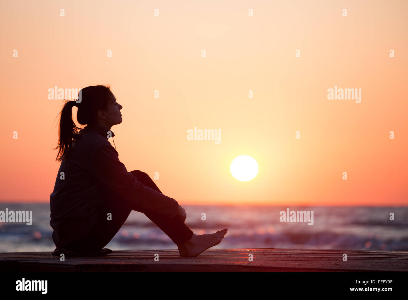 Lonely girl sitting on the sunrise beach woman silhouette over sunrise sky stock image
