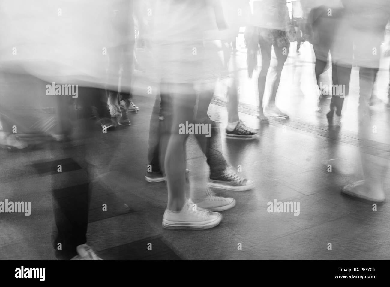 Motion blur crowded people walking in fashion mall in black and white - Stock Image