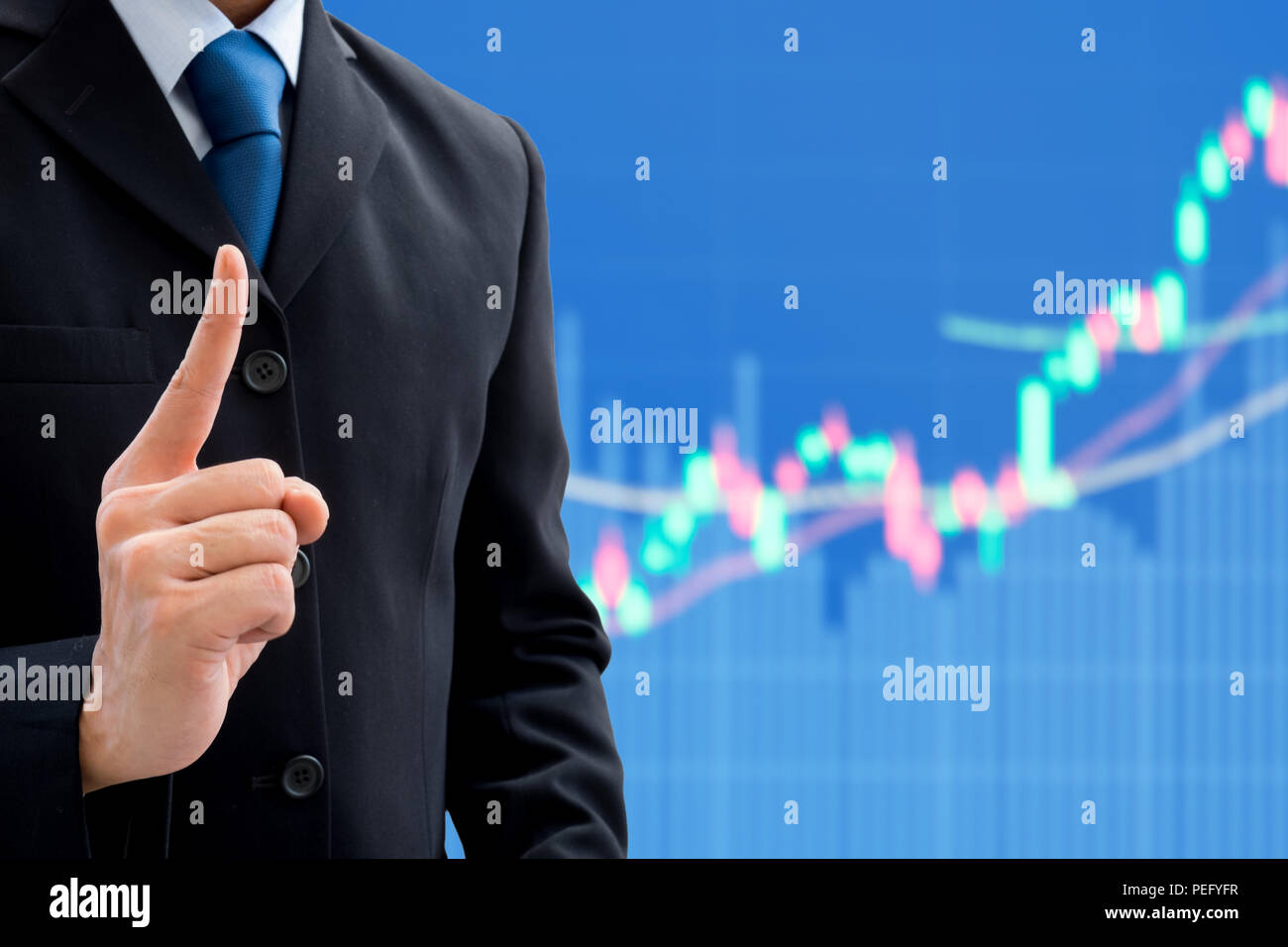 Businessman in dark gray suit raising his pointing finger showing that he is getting an idea and strategy to success in business. Business and stock m - Stock Image