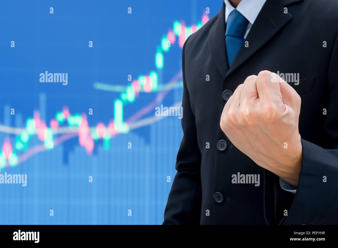 Businessman in dark gray suit raising his fist of success and victory in global business. Increasing up business and stock market graph in background - Stock Image