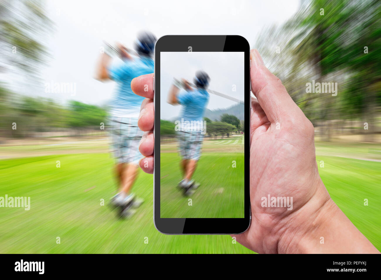One using camera in smartphone capture still photo and record motion video when other swinging on golf teeing ground. - Stock Image
