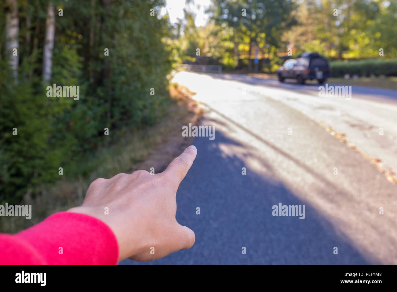 Person's hand and index finger pointing straight ahead on a street, giving directions Stock Photo