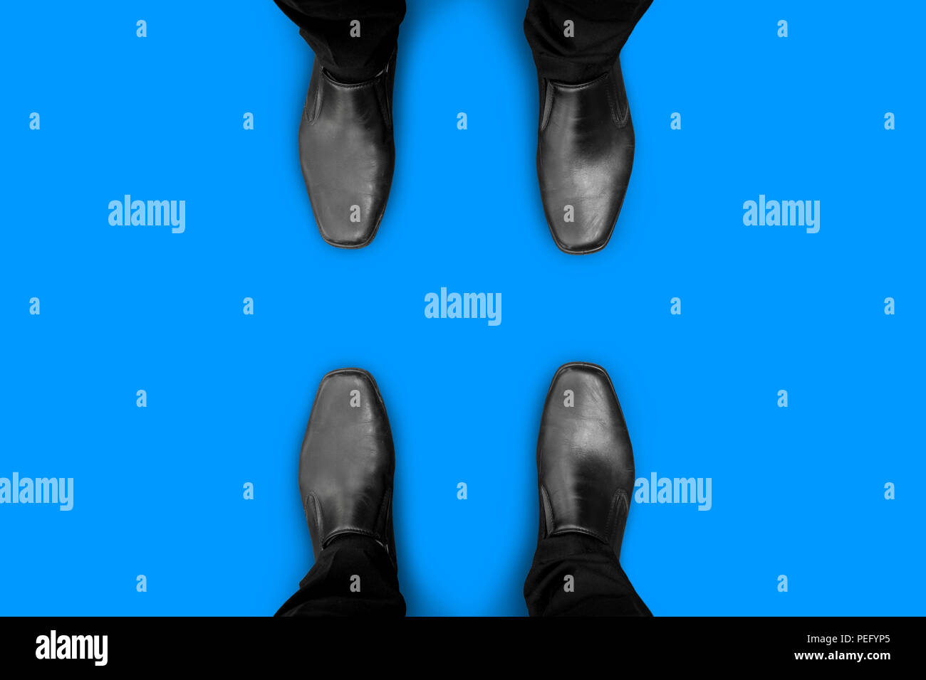 Two businessmen in black shoes standing on opposite sides. They are competitors, friends, rivals, enemies or partner. - Stock Image