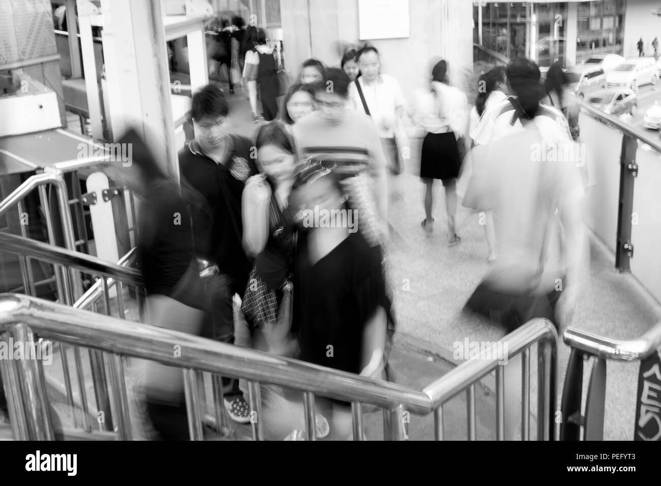 Motion blur people walking on sky walking path to cross the street in Bangkok, Thailand. Black and white filter. - Stock Image