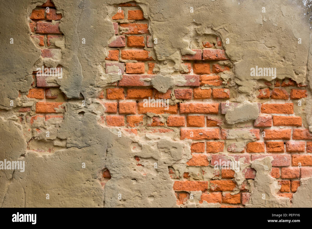 crumbling render or plaster coming off of red brick wall. Building maintenance and plastering or rendering falling off of a wall. - Stock Image
