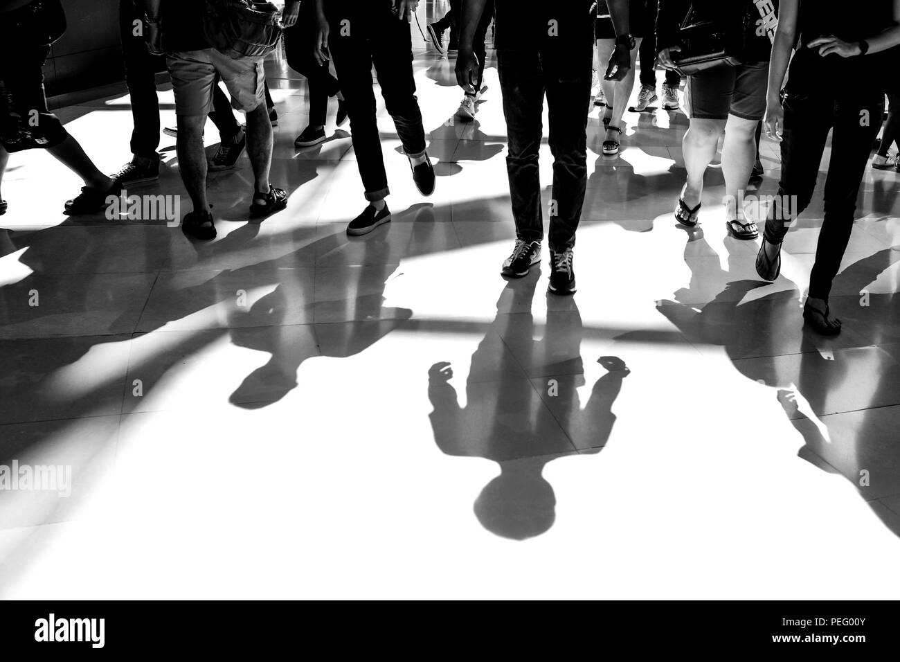 People walking and sunlight shining from behind making shadow on the floor. Black and white filter effect. - Stock Image