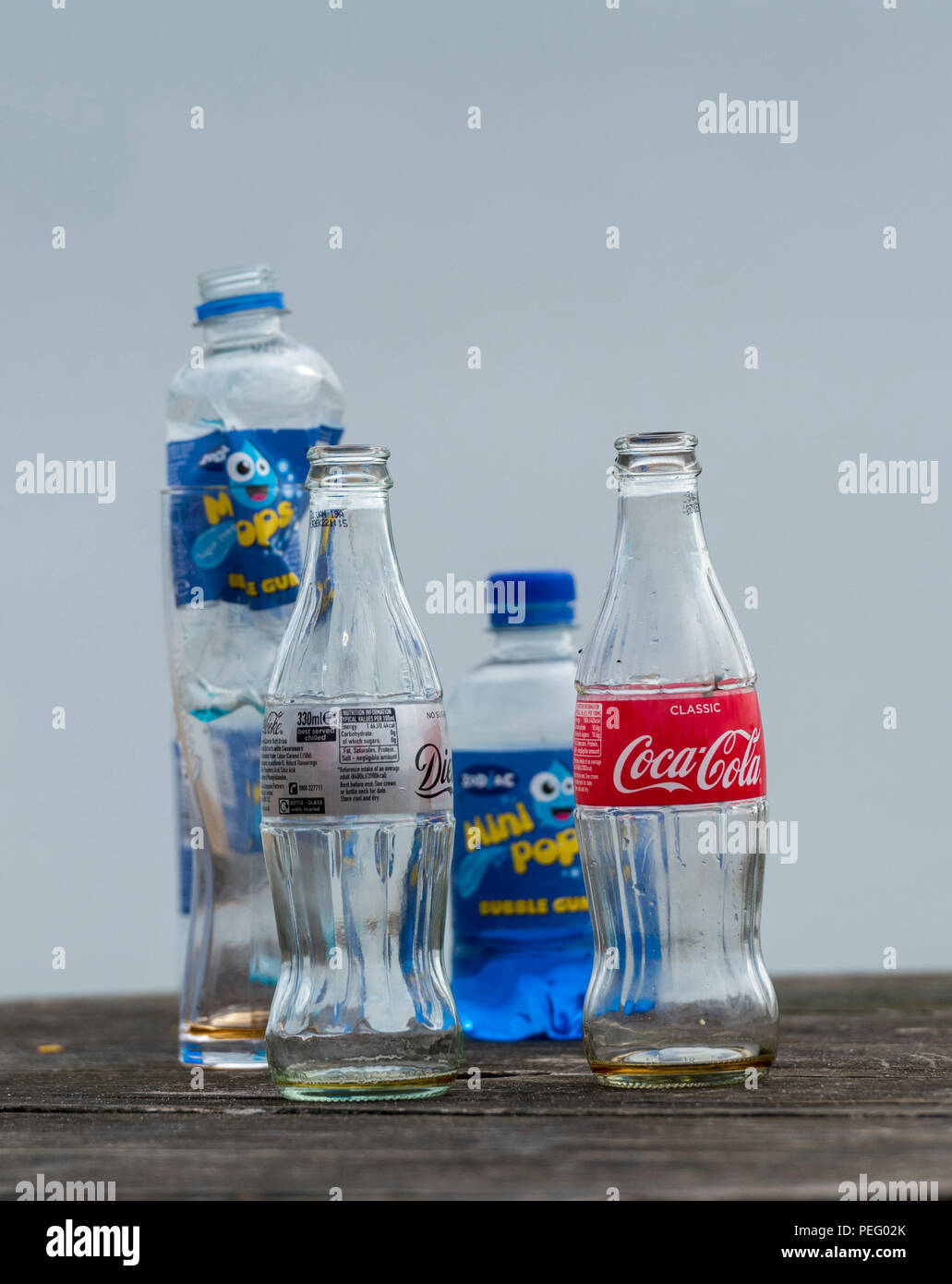 plastic and glass bottles left on a bench at the seaside polluting and littering the countryside. - Stock Image
