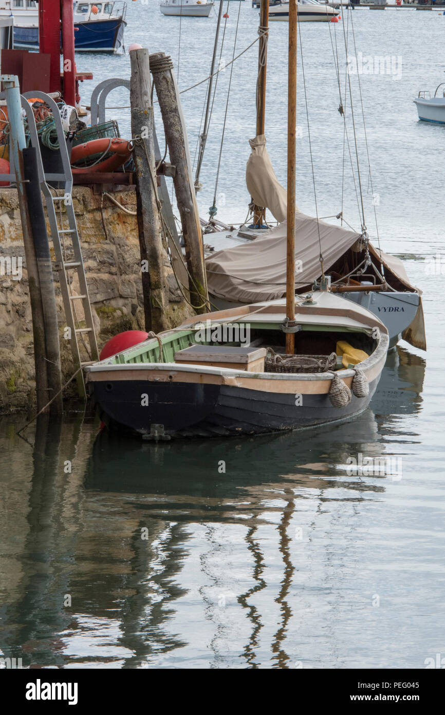 an old or traditional sailing dinghy alongside a wall in the harbour at bembridge on the isle of wight - Stock Image