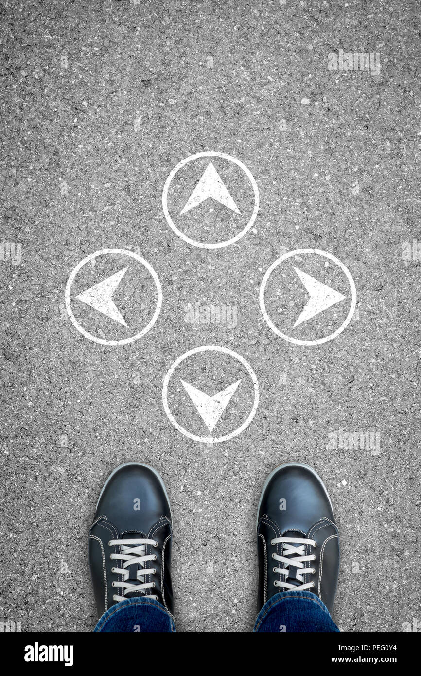 Black casual shoes standing at the crossroad making decision which way to go. - Stock Image