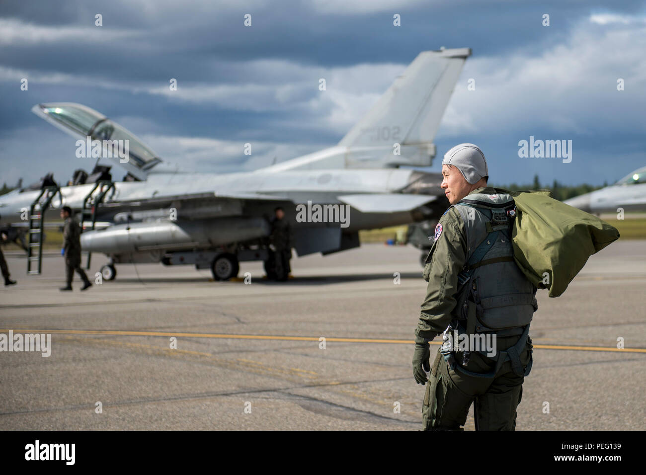 Republic of Korea air force (ROKAF) Maj. Lee Dong Seop, a ROKAF F-16D Fighting Falcon pilot, carries equipment to his aircraft, Aug. 11, 2015, prior to the launch of a RED FLAG-Alaska (RF-A) 15-3 sortie from Eielson Air Force Base, Alaska. The ROKAF flew a squadron of F-16Ds across the Pacific Ocean to train in the Joint Pacific Alaska Range Complex's 67,000 square miles of airspace for two weeks of realistic combat flying training throughout RF-A 15-3. (U.S. Air Force photo by 1st Lt. Elias Zani/Released) - Stock Image