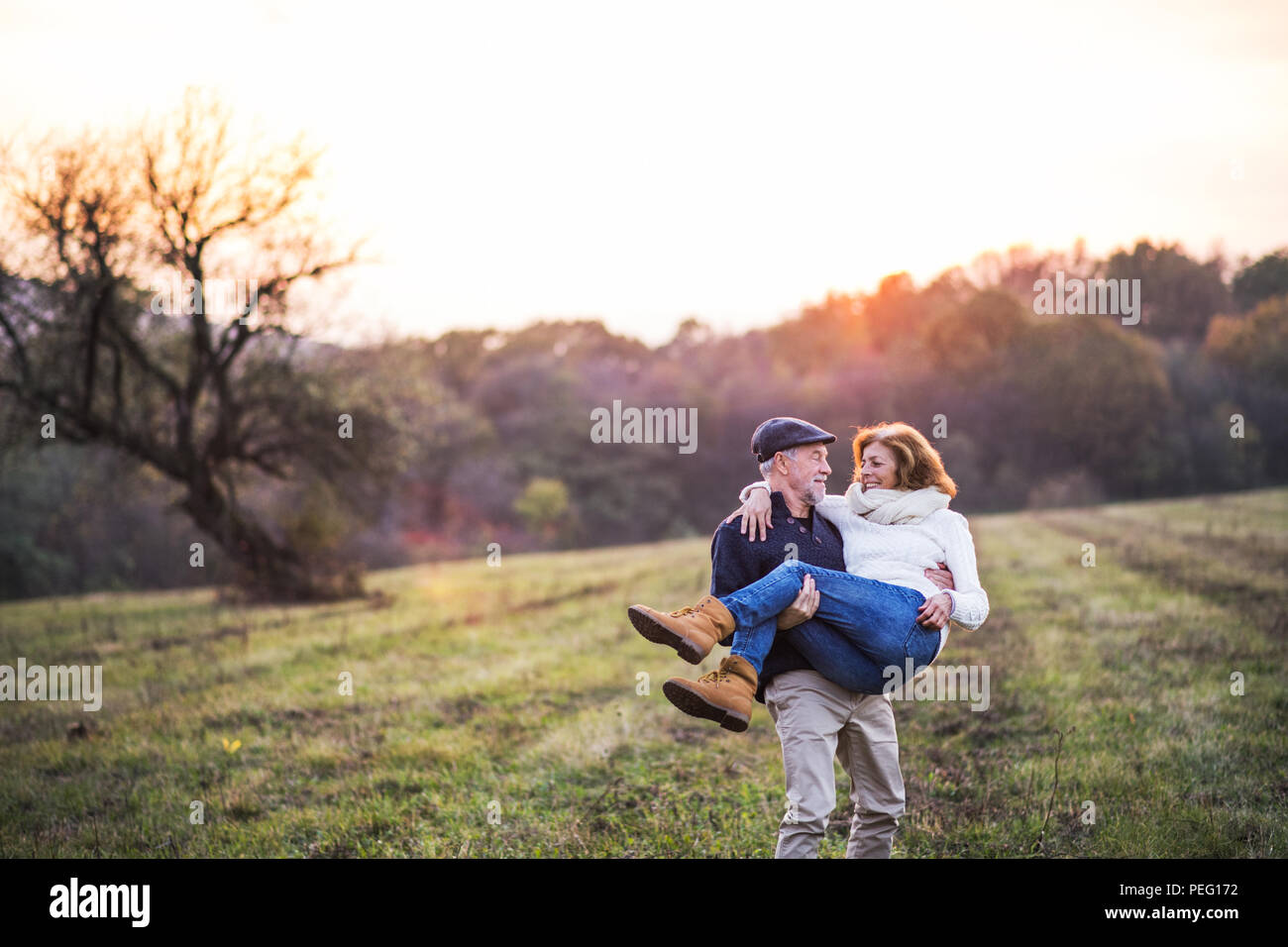 Senior man carrying a woman in his arms in an autumn nature at sunset. - Stock Image