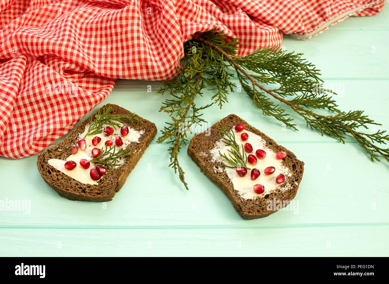 black bread with grenades berries on turquoise wooden background christmas food christmas decorations with lemon juniper branch red berries