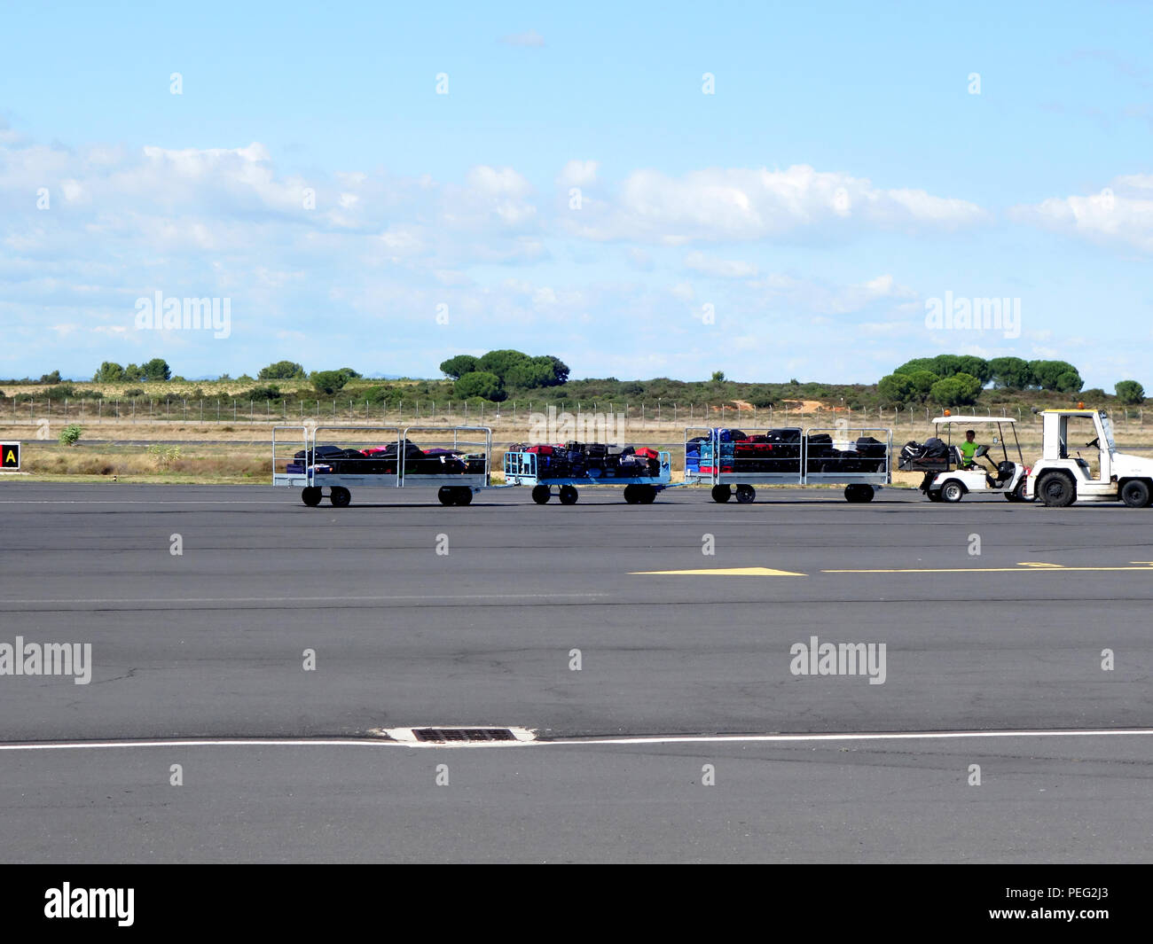Airport apron tractor and carts carry baggage to be put on a conveyor into a plane at Beziers Cap d'Agde Airport, France - Stock Image