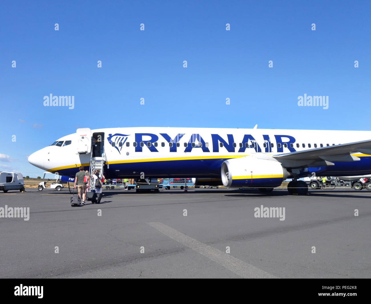 Passengers walking across the tarmac towards their homeward flight on a Ryanair plane - Stock Image