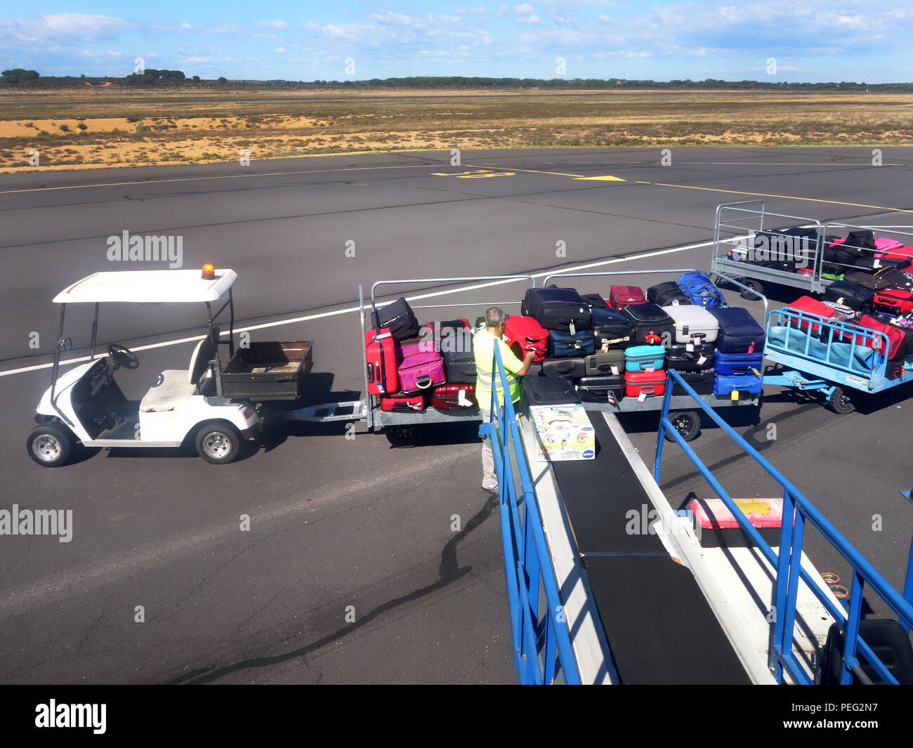 Airport handler loading baggage being put on a conveyor into a plane at Beziers Cap d'Agde Airport, France - Stock Image