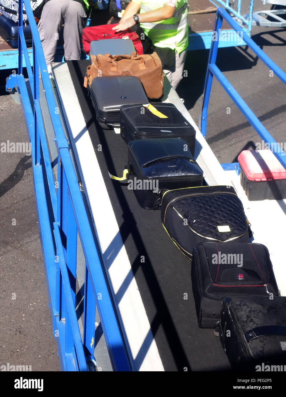 Baggage being put on a conveyor into a plane at Beziers Cap d'Agde Airport, France - Stock Image