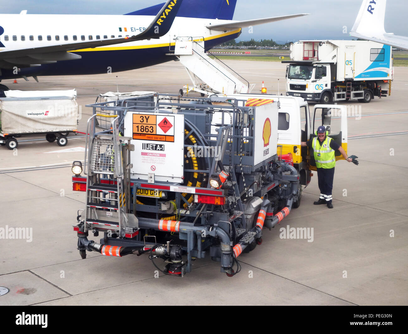 Airport worker starting the aviation refuelling of a plane at Manchester International Airport. image shows a fuel truck with plane also in shot - Stock Image