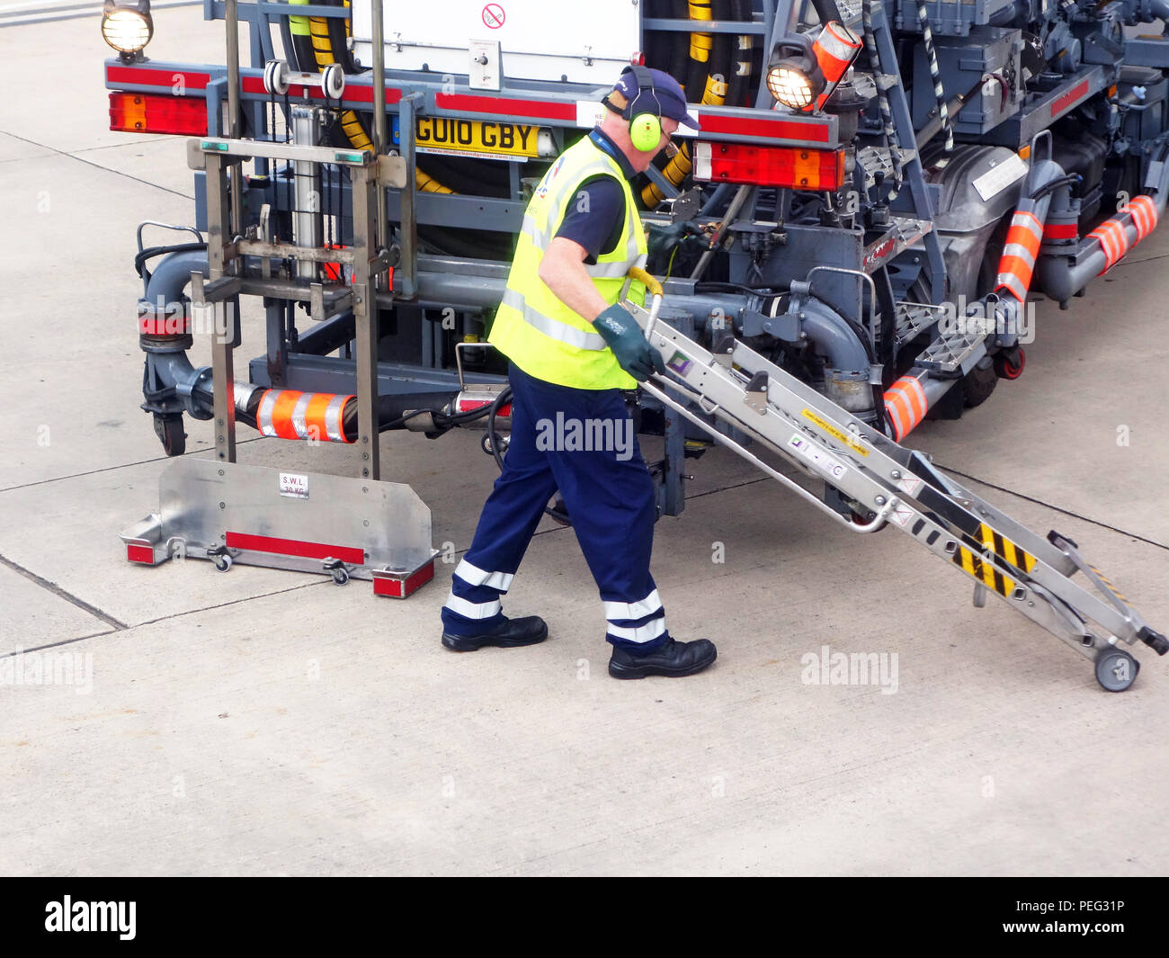 Closeup of a male Airport worker starting the aviation refuelling of a plane at Manchester International Airport - Stock Image
