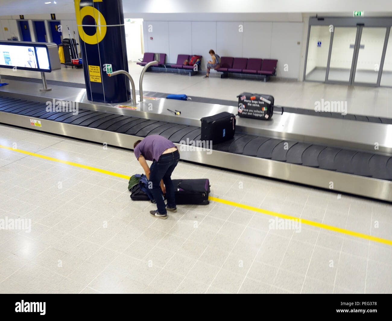 Male traveller waiting at collection conveyor belt number 6 in Terminal three at Manchester International Airport Arrivals Hall - Stock Image