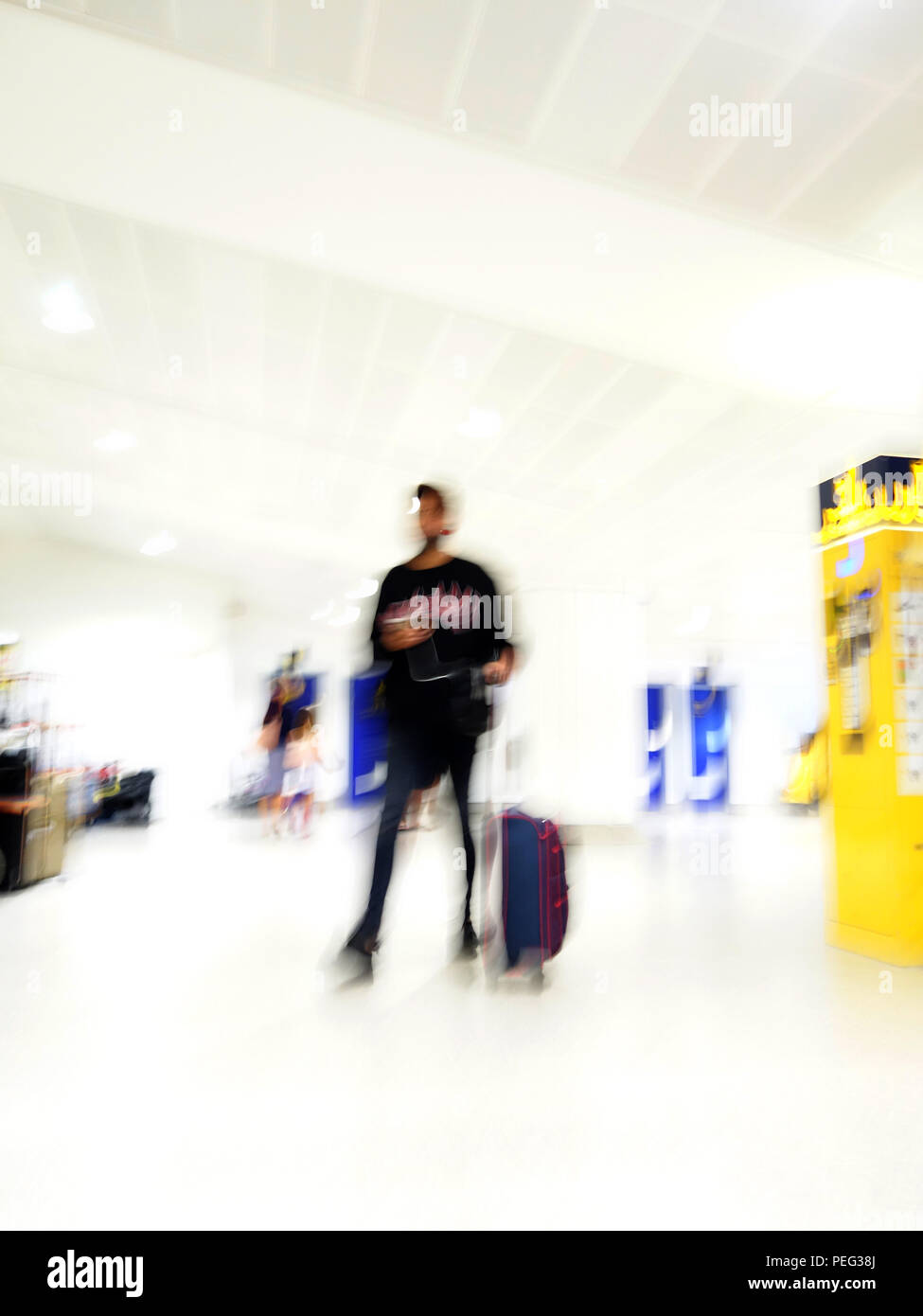 Tall male passenger moving fast through the arrivals area at Manchester International Airport - Stock Image