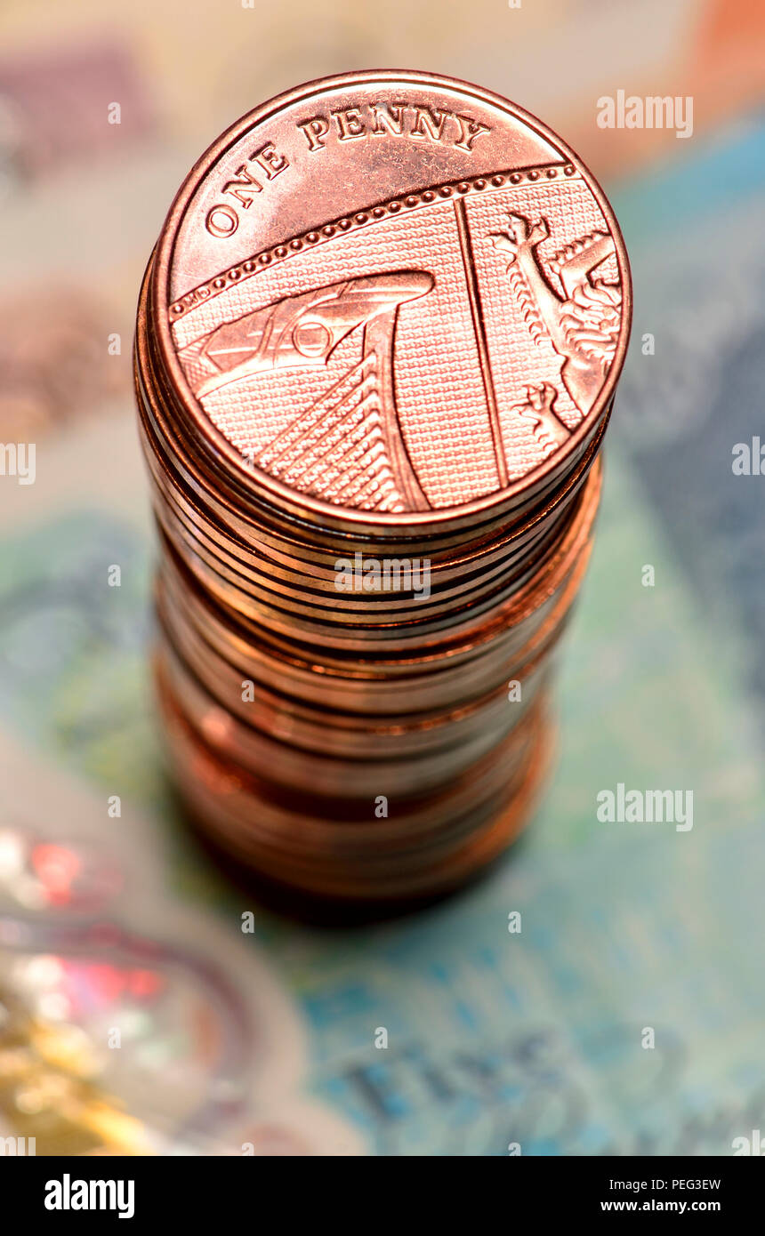 Pile of British pennies on banknotes - Stock Image