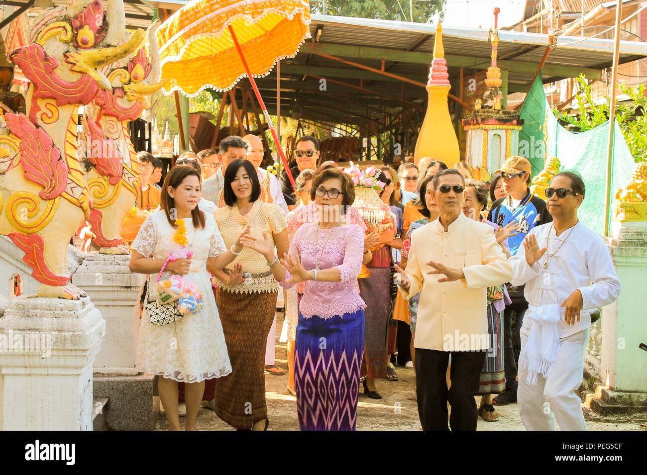 Ubon ratchathani, Thailand -  Group of Thai people seriously dancing together to celebrate their relatives ordaining at Thai temple. - Stock Image