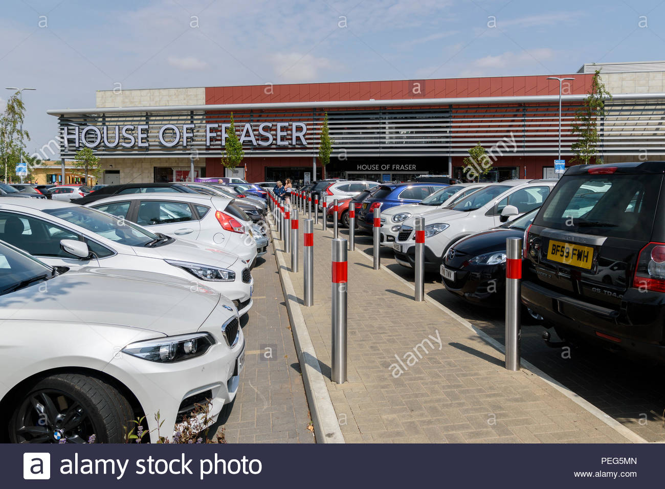 Walkway between parked cars leading to House Of Fraser store in Rushden Lakes, Northamptonshire, England, UK - Stock Image