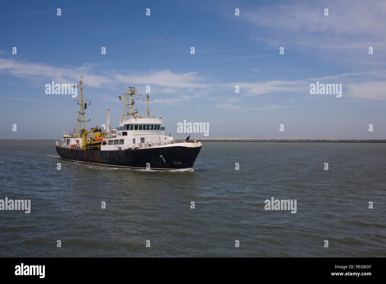 Trawler with black lower and white upper coming towards land at Ostend - Stock Image