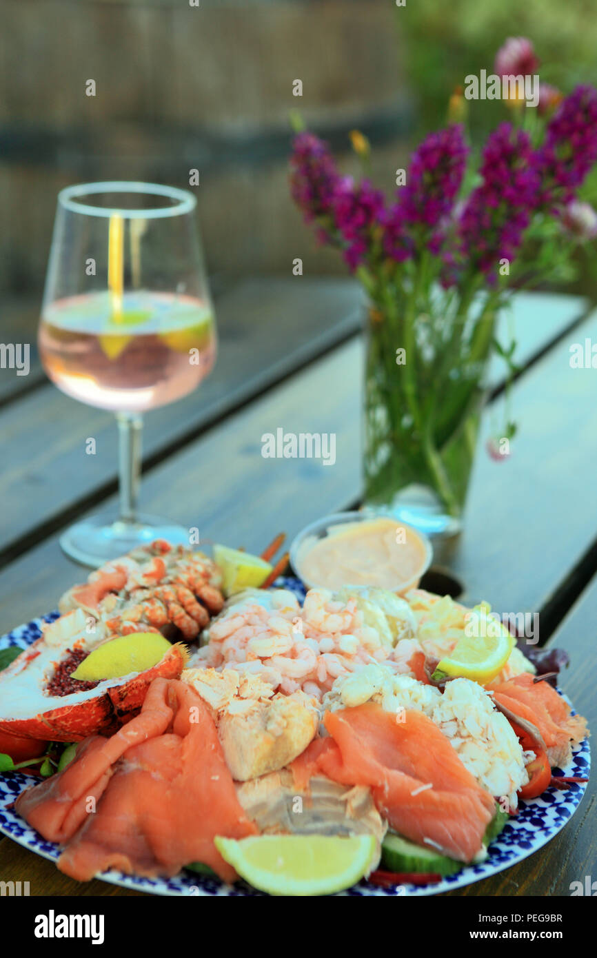 Scottish Seafood platter on an outdoor table with an alcoholic drink and a vase of wild orchids - Stock Image
