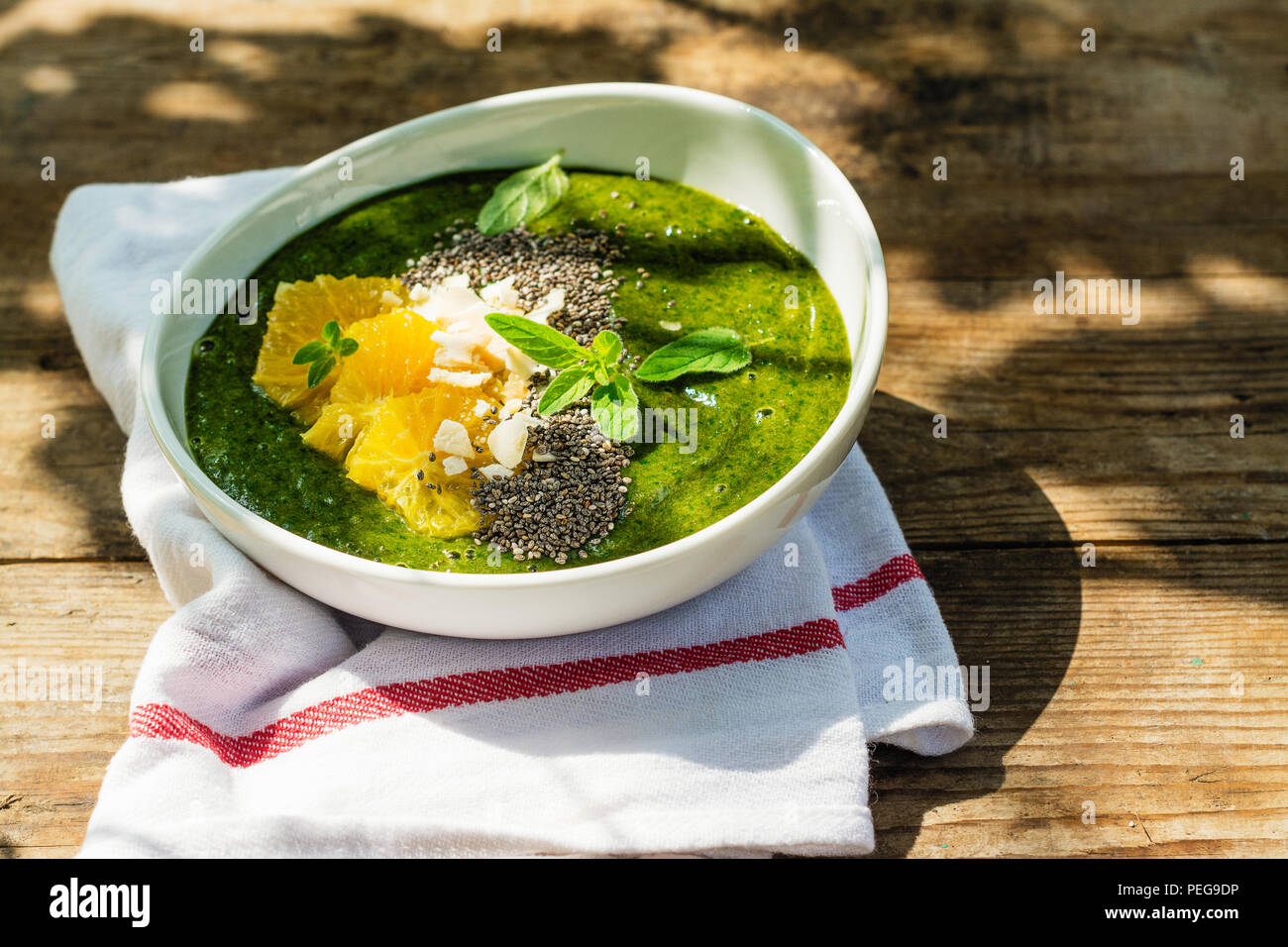 Green smoothie bowl with banana, spinach, chia seeds and oranges - Stock Image