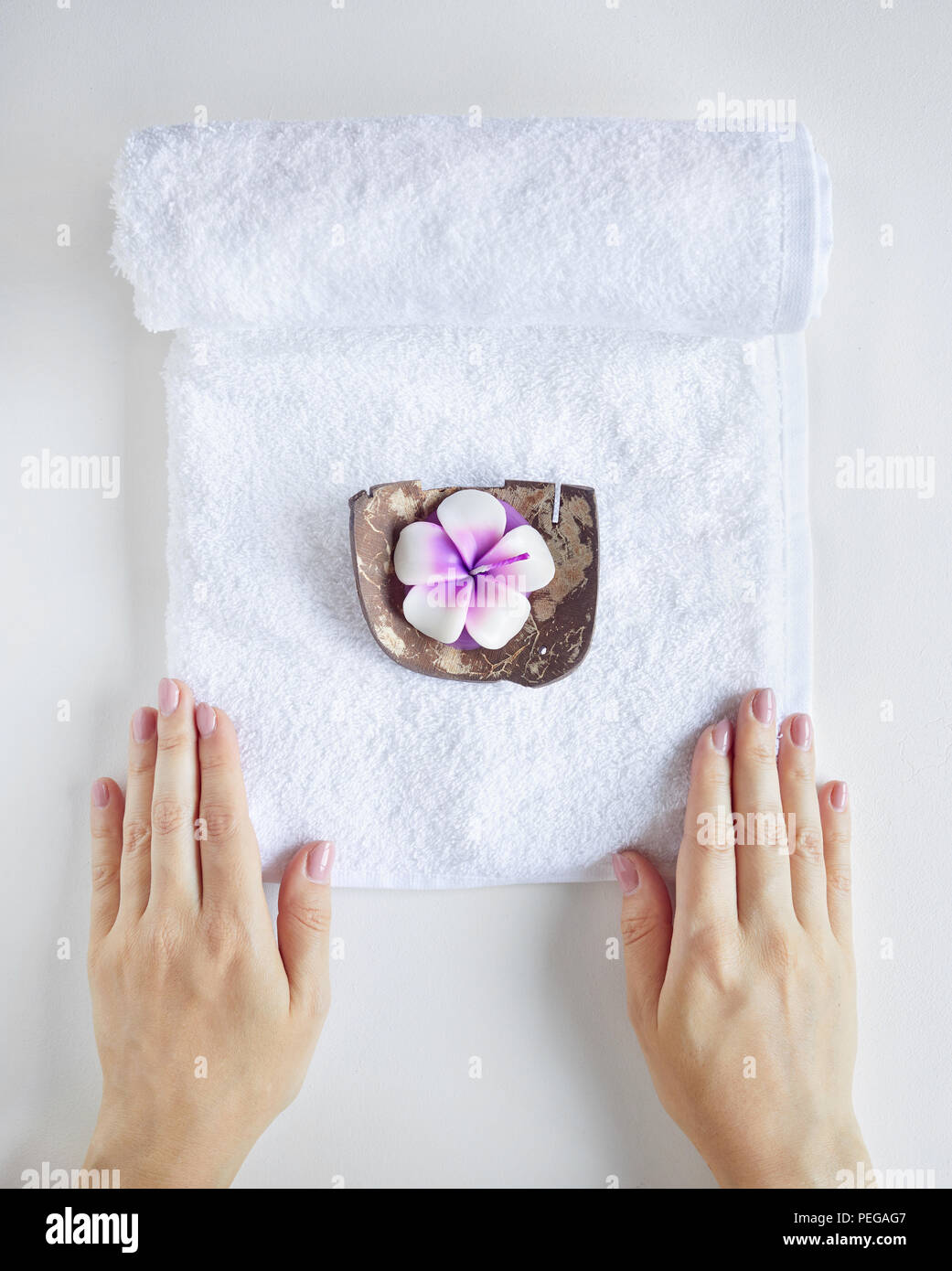 Spa and treatment. Woman holding white towel with violet candle on white plain background - Stock Image