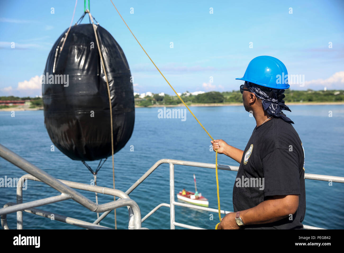 150815-M-GO800-125 SAN FERNANDO CITY, Philippines (August 15, 2015) – Civilian Mariner Michael Lee pulls in a buoy aboard the Military Sealift Command joint high speed vessel USNS Millinocket (JHSV 3), Aug. 15. The Millinocket is currently underway en route to Vietnam, the final stop in Pacific Partnership 2015. Task Force Forager, embarked aboard Millinocket is serving as the secondary platform for Pacific Partnership, led by an expeditionary command element from the Navy's 30th Naval Construction Regiment (30 NCR) from Port Hueneme, California. Now in its 10th iteration, Pacific Partnership  - Stock Image