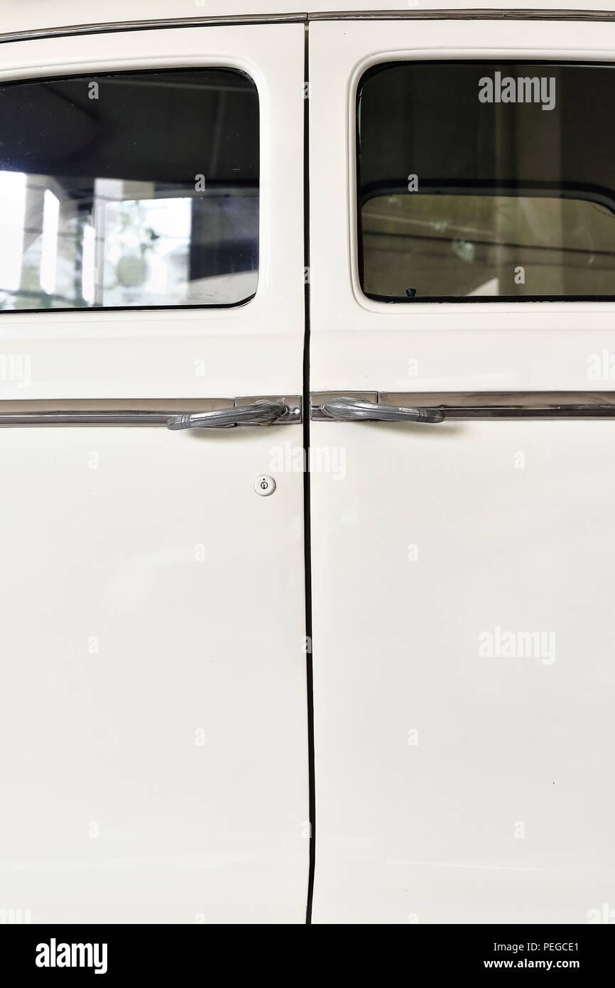 Side view of ivory-painted body of vintage car of the 1940s with rear suicide doors-left side doors closed-chrome door handles nowadays working as cla - Stock Image
