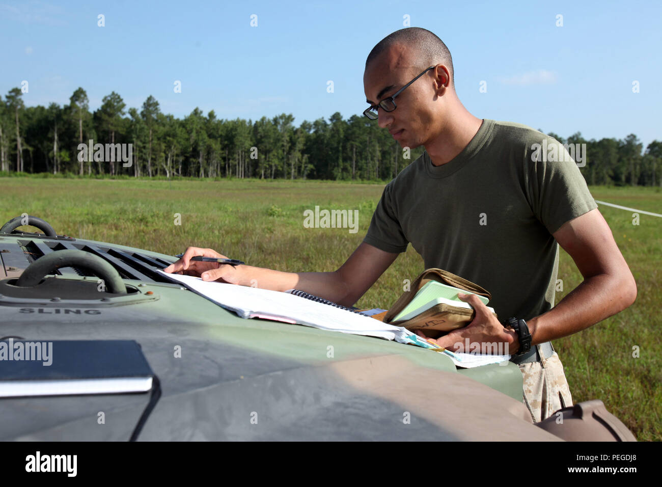 Lance Cpl. Nicholas Lewis goes over schematics for the equipment used during Marine Wing Communications Squadron 28's field training exercises at Camp Davis and Outlying Landing Field Atlantic, North Carolina, Aug. 12, 2015. The training served as a refresher course and is typically held anywhere from two to three times per year for tropospheric scatter radio multi-channel equipment-related military occupational specialties in the squadron. Lewis is a digital wideband repair technician with MWCS-28. - Stock Image