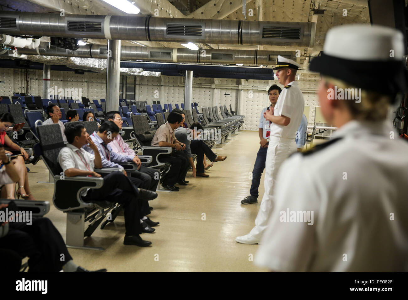 150818-M-GO800-024 DA NANG, Vietnam (Aug. 18, 2015) – Lt. j.g. Mark Roach explains to local Vietnamese officials the function of the 312 room aboard the Military Sealift Command joint high speed vessel USNS Millinocket (JHSV 3) during a ship tour Aug. 18. Task Force Forager, embarked aboard the Millinocket  is serving as the secondary platform for Pacific Partnership, led by an expeditionary command element from the Navy's 30th Naval Construction Regiment (30 NCR) from Port Hueneme, Calif. Now in its 10th iteration, Pacific Partnership is the largest annual multilateral humanitarian assistance - Stock Image