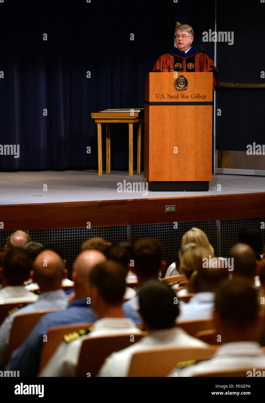 Stanley Carpenter, professor and historian for U.S. Naval War College (NWC), provides the history of NWC to students, staff, faculty and guests during a convocation ceremony kicking-off the 2015-2016 school year. During the ceremony, Rear Adm. P. Gardner Howe III, president, NWC, presented Adm. Michael S. Rogers, commander, U.S. Cyber Command, director, National Security Agency, chief, Central Security Service, the 2015 Distinguished Graduate Leadership Award. The award honors NWC graduates who have earned positions of prominence in the national defense field.  (U.S. Navy photo by Chief Mass C - Stock Image