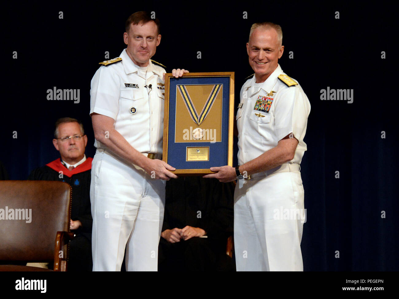Rear Adm. P. Gardner Howe III (right), president, U.S. Naval War College (NWC), presents Adm. Michael S. Rogers, commander, U.S. Cyber Command, director, National Security Agency, chief, Central Security Service, the 2015 Distinguished Graduate Leadership Award  (DGLA) during a convocation ceremony at NWC in Newport, Rhode Island. During the ceremony, Rogers provided a keynote address and was presented the 2015 DLGA.  The award honors NWC graduates who have earned positions of prominence in the national defense field.  (U.S. Navy photo by Chief Mass Communication Specialist James E. Foehl/Rele - Stock Image